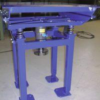 Problema: Un material tenpia que ser compactado a travez de un transportador. Solución: Una mesa especialmente diseñada para permitir que la parte superior fuera sacudida por un Oscilador NTK 40. El tramo del retorno pasa por en medio de la mesa.